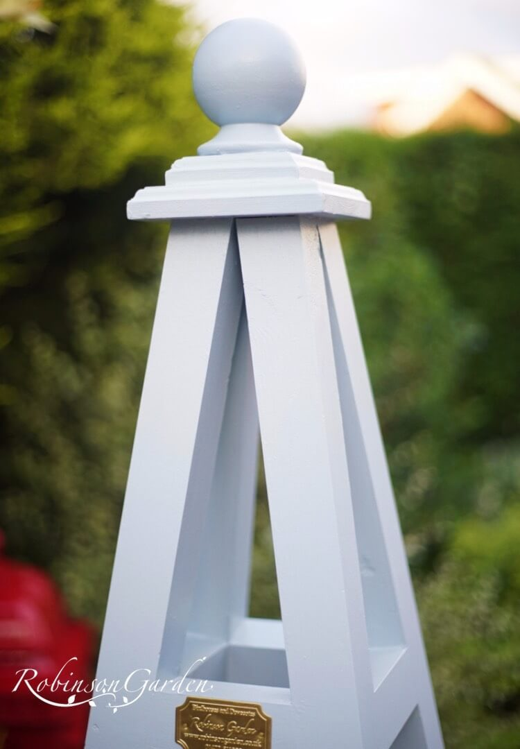 Bespoke wooden garden obelisk design hand painted in Lincolnshire, England, UK using Farrow & Ball exterior eggshell paint. Uniquely crafted using sustainable FSC certified timber / wood. Available in a range of sizes including 5ft (5 foot), 6ft (6 foot) and 7ft (7 foot) as well as trellised design, 8ft design available on request. We sell small garden obelisk, large garden obelisk and tall garden obelisk, The wooden obelisk design is different to Argos, B&M, ALDI, homebase, dobbies, gardman, home bargains, pets at home, B&Q, b & q, amazon, M&S, Robert dyas, rspb, ikea, john lewis, rhs, gumtree, asda, argos, wilkinsons, kingfisher, the garden obelisk company, QVC or any other garden centre. We are an online only store and we are not on the high street. We also have outlet shops across etsy and ebay UK. Not made from metal or copper. Our design plan, dimensions and height are suitable for climbing plants including Roses, sweet peas and is freestanding and a perfect gift for garden lovers. Wooden garden obelisk assembly free and no set up required. Visit out gallery to see all the wooden obelisk images. Wooden obelisk / garden obelisk delivered ready assembled. Perfect bird table for your garden, choice of ball, acorn and unique finial. Designs include Windsor wooden obelisk and Buckingham wooden obelisk. A smart English garden eiffel obelisk. Can be purchased as a set of 3 for your garden.